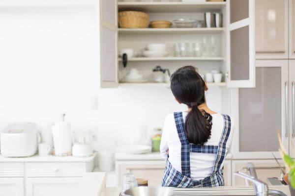 Woman with her back to us, looking at a tidy open kitchen cabinet with plates, bowls and cups in it. | konmari method