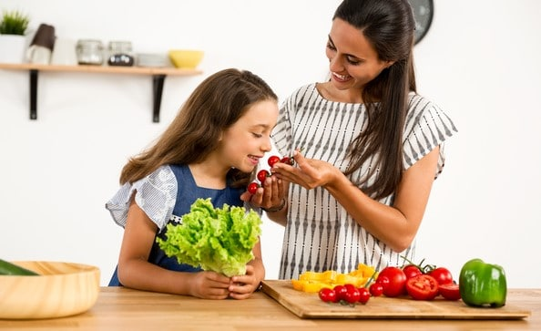 Mom and 9 year old daughter smiling and smilling cherry tomatoes while they chop vegetables. | meal planning course