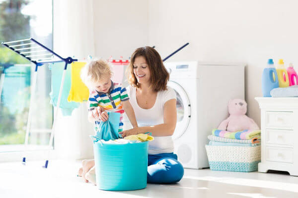 Mom and her two year old son sit on  the laundry room floor and happily sort through clothes. | organize kids clothes