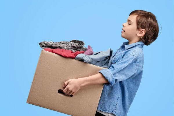 7 year old boy carrying a cardboard box full of clothes. | organize kids clothes