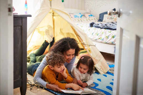 Mom and two young kids laying on their bellies on the floor, reading a book. | organized kids room