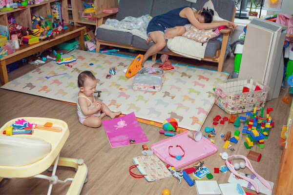 Messy room with toys strewn across the floor. Overwhelmed mom lays on the couch and baby girl sits on the floor, playing. | organized kids room