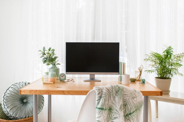 Neat minimalist desk with a potted plant, computer, coffee mug, small clock and a few notebooks neatly arranged on the top. | overwhelmed by a messy house