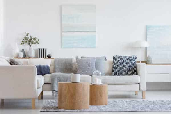 Clutter free home with two wooden coffee tables with plant in pot in front of grey corner sofa in fashionable living room interior.