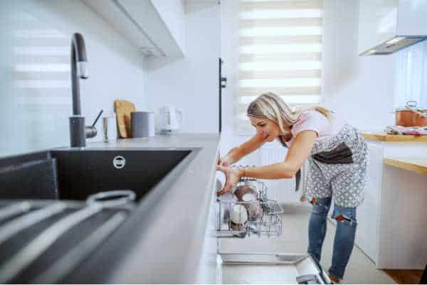 Woman loading the dishwasher in her clutter free home kitchen.