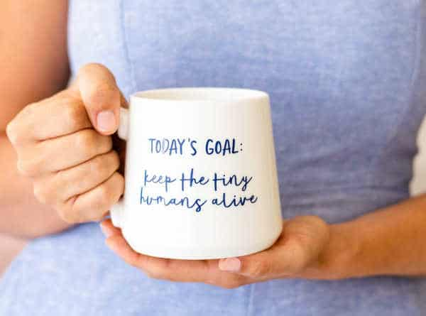 """Close up of a woman hands holding a mug that says """"Today's goal: Keep the tiny humans alive."""" 