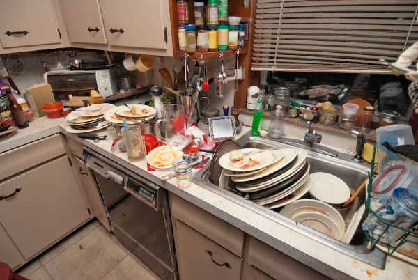 Cluttered kitchen with counter full of dirty dishes.
