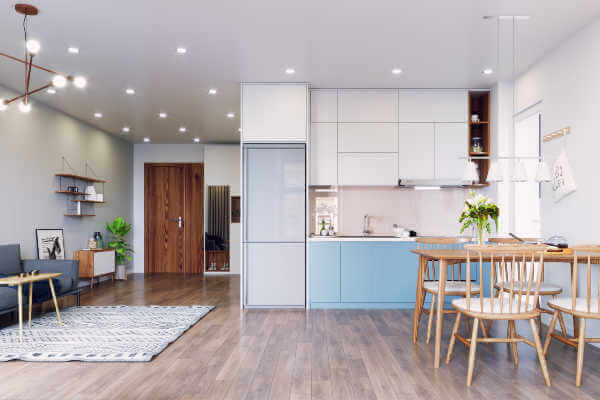 Tidy open concept kitchen and living room, with a wood table and 4 wood chairs, a kitchen in the background and a couch off to the left.   not a cluttered kitchen