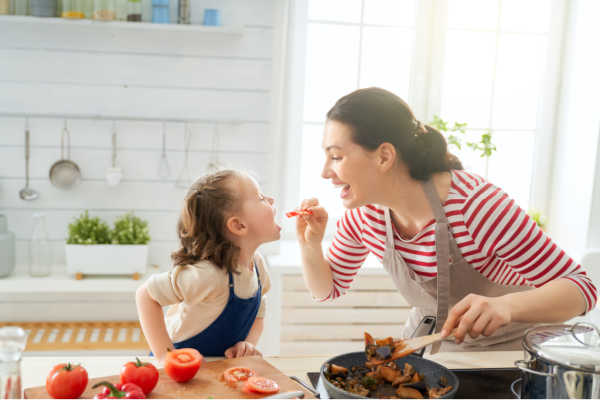 Mom and her 4 year old daughter happily cooking in the kitchen. | not a cluttered kitchen