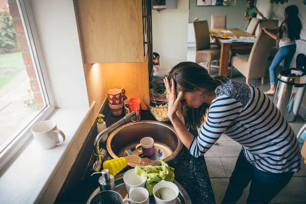 Overwhelmed woman leaning over a kitchen sink filled with dirty dishes. | declutter fast