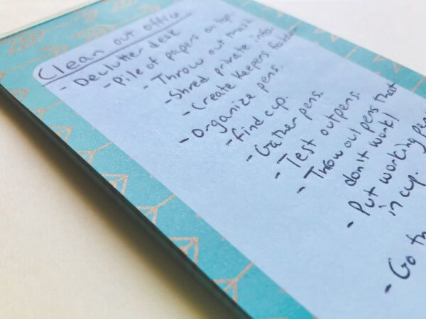 Decluttering checklist written on a small notepad. The example steps are the same as the ones listed below in the post.  | steps to declutter your home
