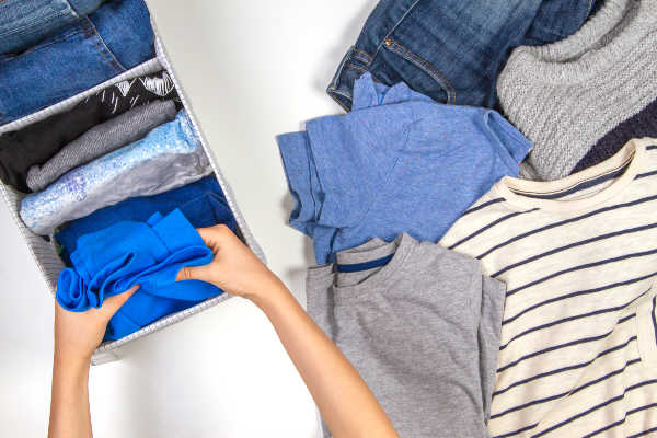Woman folding clothes and stacking them neatly in a cubby organizer. | steps to declutter your home