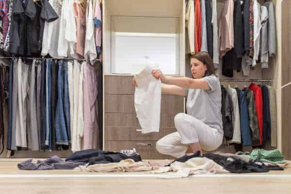 A woman squats in her large, walk in closet, holding up a pair of shorts to figure out if she wants to keep it. A pile of too many clothes lays around her on the floor.