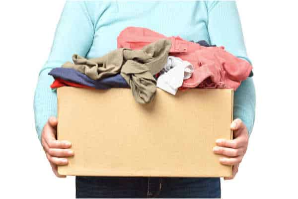 Woman holding a cardboard box with too many clothes spilling out of it.
