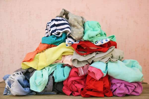 A pile of unfolded clothes. | too many clothes