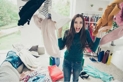 Woman throwing clothes onto a pile of clothes on the floor.